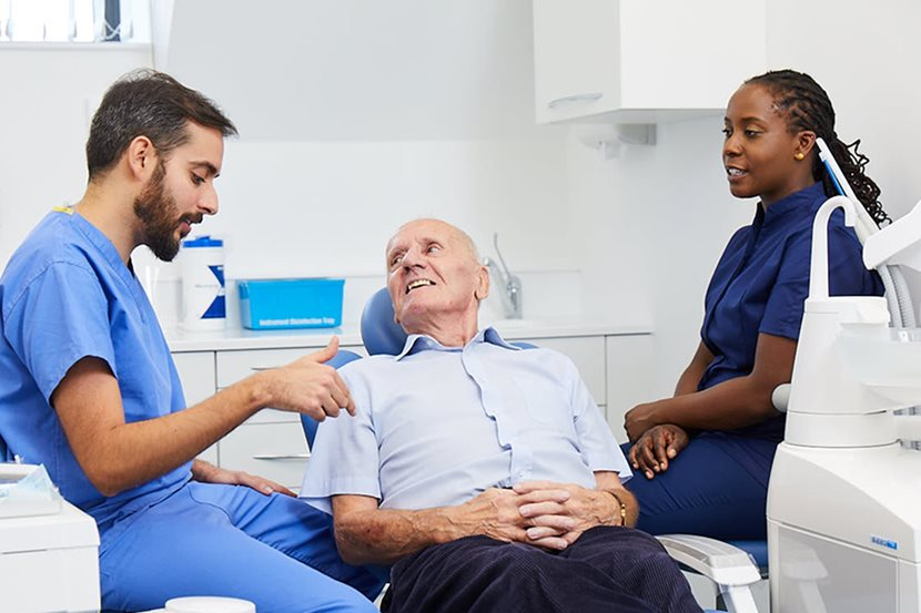 Dentist explaining treatment to senior patient