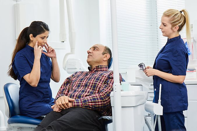 Dentist explaining to patient how root canal treatment works
